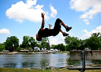 Josh Peckler - Jpeckler@shawmedia.com Jose Leon of Cary does a back flip off a bench in front of the Fox River as he participates in a art fair along the Fox River in Fox River Grove Sunday, July 15, 2012.