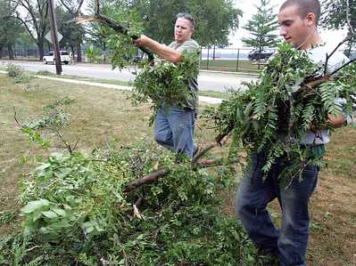 H. Rick Bamman -hbamman@shawmedia.com Crystal Lake park district workers Kyle Berge (left) and Andrew Guminski clear branches Thursday in the lot at Country Club Road and Lake Ave. The high winds and heavy rains Wednesday night struck Main Beach and wrapped around the southeastern portion of the lake about 10 blocks into Lakewood.