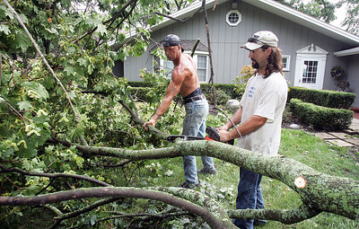 H. Rick Bamman -hbamman@shawmedia.com Tree removal crew John Fox (left) and Brian Stodola clear debris Thursday at 370 S. Shore Dr. in Lakewood.