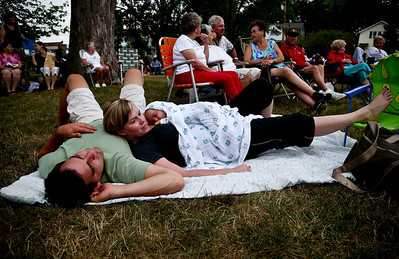 Josh Peckler - Jpeckler@shawmedia.com Molly Degroh of Mchenry lays on her husband Alex with their two-month old son Monty as they listen to music at the Fiesta Days Concert in the Park at Veteran's Memorial Park in Mchenry Thursday, July 19, 2012.