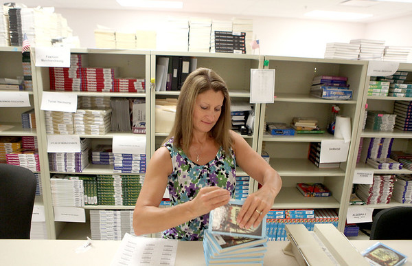 Deena Ellerbusch, book room supervisor at St. Charles East High School, applies bar codes onto books at the school Tuesday morning.