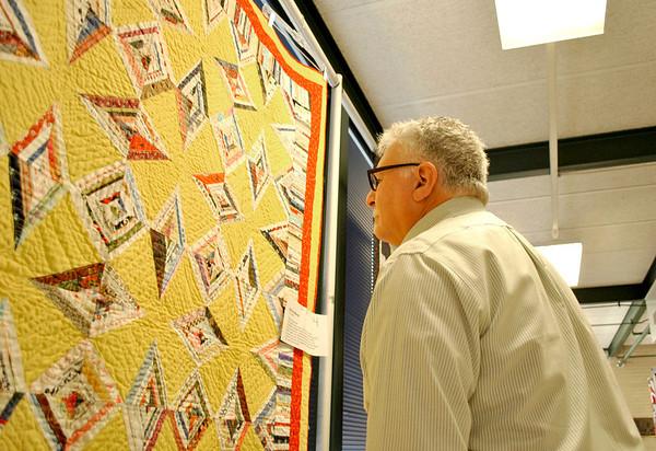 Batavia City Administrator Bill McGrath judges a quilt on behalf of Batavia mayor  Jeff Schiekle for the Mayor's Award at the Batavia Depot Museum's sixth annual quilt and textile show.
