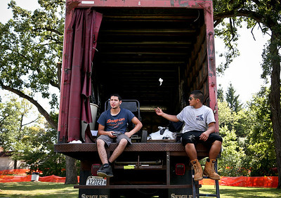 Josh Peckler - Jpeckler@shawmedia.com Esteban Gonzalez (left) and Adrian Mora, both of Carpentersville sit on a truck gate as they wait to set up a tent for Algonquin Founders' Days at Towne Park in Algonquin Wednesday, July 25, 2012. Founder' Day opens today and will run through out the weekend.