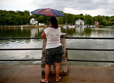 Josh Peckler - Jpeckler@shawmedia.com A women watches as rain clouds pass the Fox River as it rains during the Algonquin Founders' Days Cardboard Boat Regatta in Algonquin Thursday, July 26, 2012.