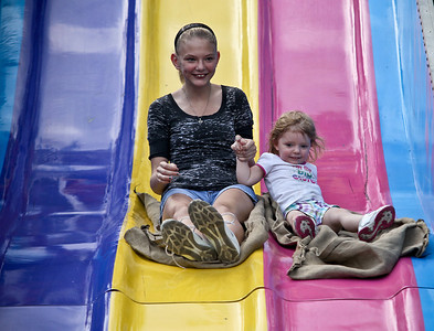Josh Peckler - Jpeckler@shawmedia.com Elizabeth Breyette, 13 and Kara Peterson, 2 both of Gilberts go down a slide during the special needs carnival at the Algonquin Founders' Days held at Towne Park in Algonquin Thursday, July 26, 2012.