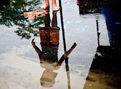 Josh Peckler - Jpeckler@shawmedia.com Elliot Doulet, 3 of Paris, France is reflected in a puddle after it rained during the Algonquin Founders' Days Cardboard Boat Regatta in Algonquin Thursday, July 26, 2012.