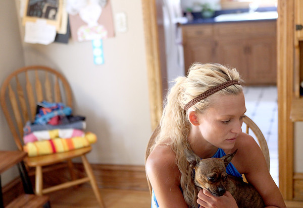 Carrie Brummel cuddles her Boston terrier/miniature pinscher mix, Bella, in the dining room of her Batavia home. Brummel, a former heroin addict, has been drug-free for 10 years and is a graduate of the Kane County Drug Court.