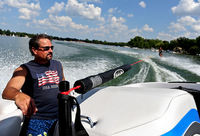 Josh Peckler - Jpeckler@shawmedia.com Ed Figel of Crystal Lake sits in the boat while friend Michael Gende of Mchenry slalom water skies at Crystal Lake Sunday, July 15, 2004. The Crystal Lake Water Ski Association hosted a slalom qualifier water ski tournament to provide a level playing field of fun competition for members.