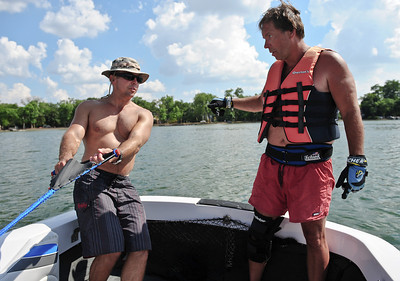 Josh Peckler - Jpeckler@shawmedia.com Rick Ridenour of Crystal Lake (left) shows Joe Doll of Downers Grove water skiing techniques while on Crystal Lake Sunday, July 15, 2004. The Crystal Lake Water Ski Association hosted a slalom qualifier water ski tournament to provide a level playing field of fun competition for members.