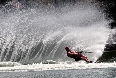 Josh Peckler - Jpeckler@shawmedia.com Eric Anderson of Crystal Lake sprays a large stream of water up as he goes around a buoy as he slalom water skies at Crystal Lake Sunday, July 15, 2004. The Crystal Lake Water Ski Association hosted a slalom qualifier water ski tournament to provide a level playing field of fun competition for members.