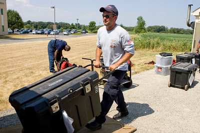 Mike Greene - mgreene@shawmedia.com Jason Henriksen, of the Lake Zurich Fire Department, loads a MABAS vehicle following a confined space training hosted by Woodstock Fire Resuce at a water booster station near Centegra Hospital Wednesday, July 18, 2012 in Woodstock. The event, which drew participants from five stations and two MABAS divisions, simulated a confined space rescue in an area no bigger than a bedroom.