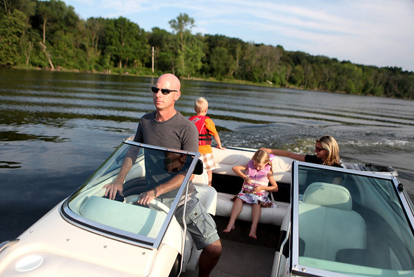Doug Denz drives his family's speed boat with his wife, Cheryl, and kids Josh, 5, and Molly, 5, on the Fox River near their home in St. Charles.  Doug and his wife, Cheryl, bought their home next to the river approximately nine years ago.