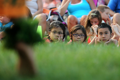Mike Greene - mgreene@shawmedia.com Raizel Andaya (left), 8, her sister Rheana, 6, and Kenji Aoki, 7, watch members of The Barefoot Hawaiian perform Tuesday, July 31, 2012 at Indian Trail Beach in Lake in the Hills. The event, hosted by the Village of Lake in the Hills, included a mix of dynamic dances, music, and vibrant costumes as well as a fire dancer.