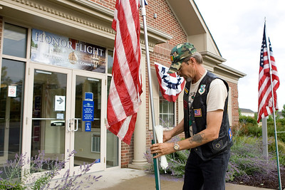 Mike Greene - mgreene@shawmedia.com Air Force Vietnam Veteran Craig Graham, of Fox River Grove, sets up flags before participants for the Honor Flight hosted by the Veterans Network Committee of Northern Illinois arrive Friday, July 27, 2012 at Fifth Third Bank in Cary. Six WWII veterans of McHenry County as well as other county's are taking the three day trip Washington D.C. to see the WWII Memorial and participate in other activities.