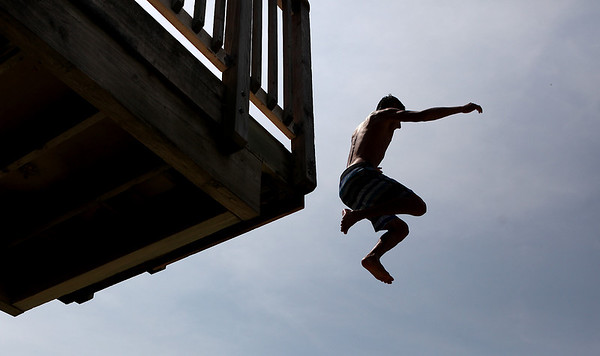 Danny Kazda, 18, leaps off of the high platform at Quarry Beach in Batavia Thursday afternoon. Temperatures were expected to reach over 100 degrees.