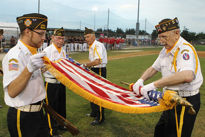 Mike Greene - mgreene@shawmedia.com Honor Guard Members Jason Moody (left) and Fredrick Nobel, a WWII veteran from the 95th division, roll up the American flag following a MCYSA/USSSA 15U Summer International Championship tribute to Armed Forces Sunday, July 29, 2012 at Lippold Park in Crystal Lake. Active and veteran armed forces members were honored before the start of featured games which were umpired exclusively by armed forces veterans.