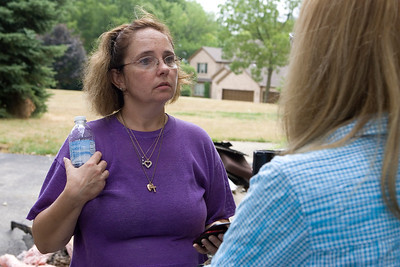 Mike Greene - mgreene@shawmedia.com Laura Kobeszko speaks with an insurance agent in Lakemoor Thursday, July 19, 2012 after a fire started when the home was hit by lightning.