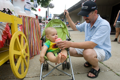 "Mike Greene - mgreene@shawmedia.com John Laskowski, of McHenry, feeds a Sno Cone to his son Nate before the start of the Annual Fiesta Days Parade Sunday, July 22, 2012 in McHenry. This year's theme for the event was ""Chambers 60th Diamond Anniversary"" with floats decorated to suit the theme."