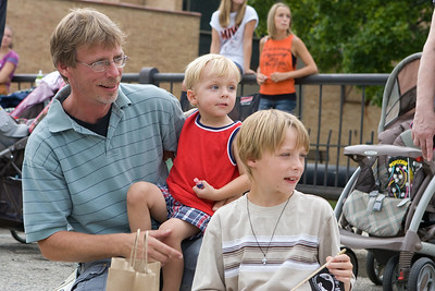 "Mike Greene - mgreene@shawmedia.com Joe Jette, of Wonder Lake, watches groups come closer with his sons Zac, 2, and Joshua, 7, during the Annual Fiesta Days Parade Sunday, July 22, 2012 in McHenry. This year's theme for the event was ""Chambers 60th Diamond Anniversary"" with floats decorated to suit the theme."