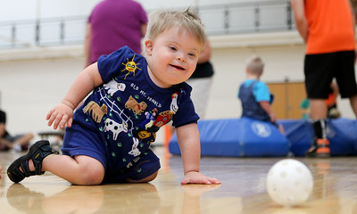 Mike Greene - mgreene@shawmedia.com 22 month-old Lukas Sanders crawls after a ball while playing during the third Annual Sports Day with GiGi's Playhouse Saturday, July 14, 2012 at McHenry East High School in McHenry. Members of the MHS football team were paired with special needs children and family members as they participated in various athletic activities.