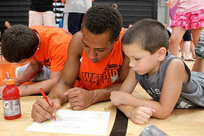 Mike Greene - mgreene@shawmedia.com Jake Braskett, 17, fills out a participation certificate with Gavin Hora, 6, during the third Annual Sports Day with GiGi's Playhouse Saturday, July 14, 2012 at McHenry East High School in McHenry. Members of the MHS football team were paired with special needs children and family members as they participated in various athletic activities.