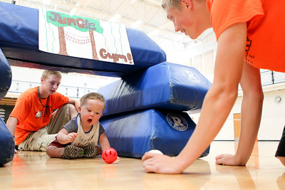 Mike Greene - mgreene@shawmedia.com Andrew Fugatt (left), 15, and Scott Marunde, 15, play with 18 month-old Will Personette during the third Annual Sports Day with GiGi's Playhouse Saturday, July 14, 2012 at McHenry East High School in McHenry. Members of the MHS football team were paired with special needs children and family members as they participated in various athletic activities.
