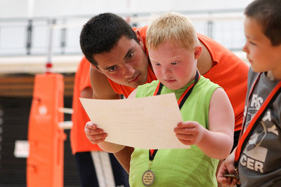 Mike Greene - mgreene@shawmedia.com Nate Rueckemann, 17, helps read over a certificate for participation with Brogan Hora, 7, during the third Annual Sports Day with GiGi's Playhouse Saturday, July 14, 2012 at McHenry East High School in McHenry. Participants received a certificate and a medal for taking part in the day's events.
