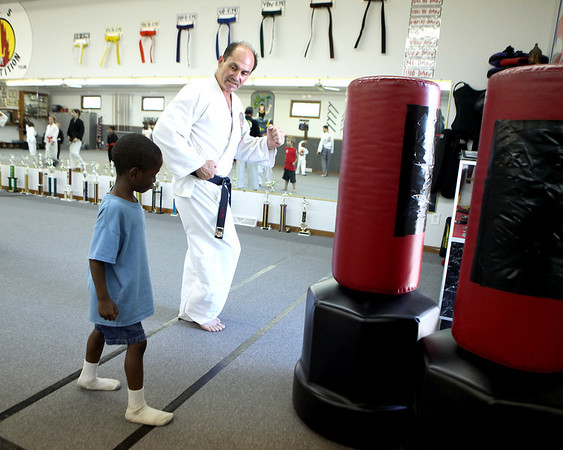 Rocky Troutman works with 5-year-old Azuri Sylvester at Rocky's Dojo and Gym in Sugar Grove Tuesday evening.