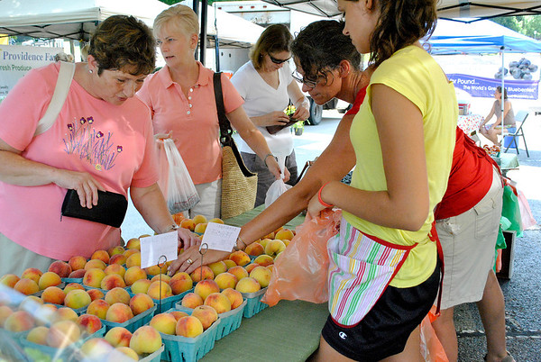 Ronni Verboom of St. Charles (far left) shops for peaches from Monica Teichman (center) and her daughter Alexis Teichman (far right) of Tree-Mendus Fruit in Eau Claire, Mich. during the St. Charles Farmers Market Friday morning.
