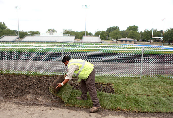 Pedro Garcia of Sebert Landscaping lays sod next to Geneva High School's Burgess Field, where new turf has been installed.