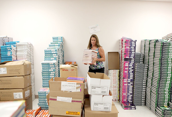 Deena Ellerbusch, book room supervisor at St. Charles East High School, packs older math books into boxes in the school's book room Tuesday morning.