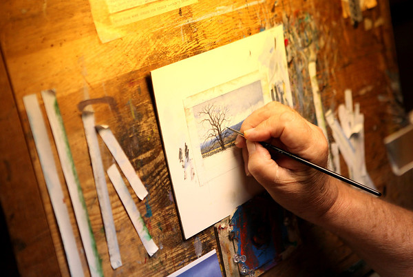 Ed Cook, an artist of miniature paintings, works in the basement studio of his Batavia home. Cook's work will be featured in the Geneva Fine Arts Festival this weekend.