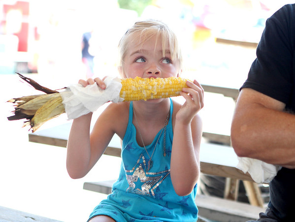Ellie Fordeck, 7, of St. Charles enjoys an ear of corn during the 2012 Kane County Fair Friday afternoon.