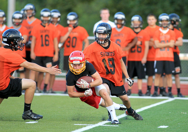 Rourke Mullins of Batavia tries to hold onto the ball under the defense of St. Charles East's Jon Finn (left) and L.J. Rutkowski during a 7-on-7 football challenge featuring Geneva, St. Charles East, St. Charles North and Batavia at Mooseheart Friday night.