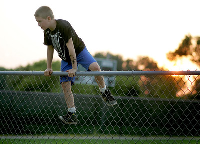 Kyle Grillot - kgrillot@shawmedia.com  Jason Montgomery, 10, of Harvard climbs a fence after retreiving a ball at Emricson Park before the start of the fireworks celebrating the fourth of July in Woodstock.