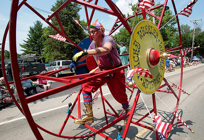 Kyle Grillot - kgrillot@shawmedia.com   A stunt man with Wacky Wheelers/Jolly Giants rolls down Dole Avenue during the Annual Independence Day Parade Sunday, July 7, 2013 in Crystal Lake. Over 100 different groups participated in the parade from City Hall to the Lakeside Festival.