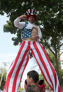 Kyle Grillot - kgrillot@shawmedia.com   A stunt man with Wacky Wheelers/Jolly Giants walks above children on the side of Dole Avenue during the Annual Independence Day Parade Sunday, July 7, 2013 in Crystal Lake. Over 100 different groups participated in the parade from City Hall to the Lakeside Festival.