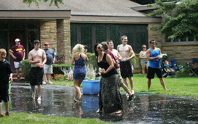 Kyle Grillot - kgrillot@shawmedia.com   Spectators take part in an annual water balloon fight held between neighbors on Dole Avenue after the the end of the Annual Independence Day Parade Sunday, July 7, 2013 in Crystal Lake. Over 100 different groups participated in the parade from City Hall to the Lakeside Festival.