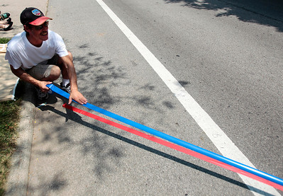 Kyle Grillot - kgrillot@shawmedia.com   Mike Funk of Crystal Lake applies tape to mark off an area for parade groups to stop and perform on Dole Avenue during the Annual Independence Day Parade Sunday, July 7, 2013 in Crystal Lake. Over 100 different groups participated in the parade from City Hall to the Lakeside Festival.