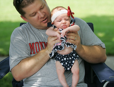 Kyle Grillot - kgrillot@shawmedia.com   Chad Steele holds his six-week-old daughter Emily Steele along Dole Avenue during the Annual Independence Day Parade Sunday, July 7, 2013 in Crystal Lake. Over 100 different groups participated in the parade from City Hall to the Lakeside Festival.