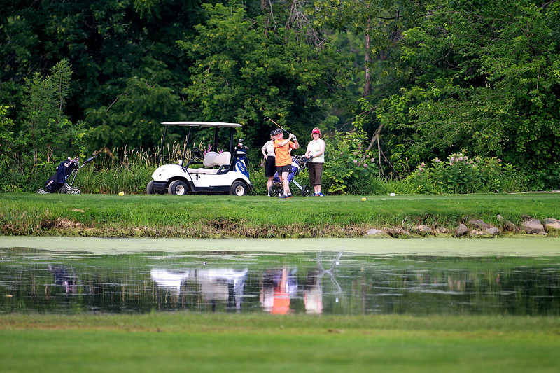 Elke Chateau of St. Charles (center) tees off as Pat Lenz and Wendy Mossier, both of St. Charles, look on during the St. Charles Women's Tournament at Pottawatomie Golf Course in St. Charles Tuesday morning.