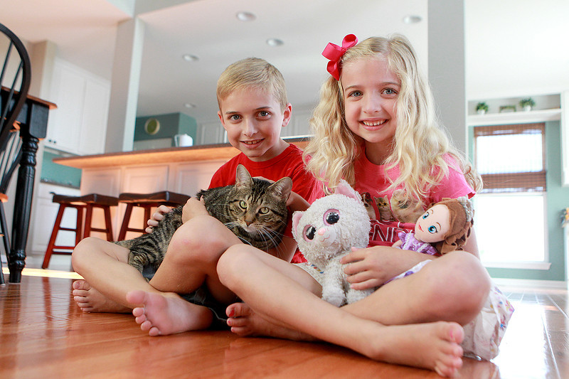 Elliot, 8, and Abigail Lechocki, 6, sit with Wilson, their cat who was rescued following a fire at their Sugar Grove home in 2011.