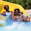 Seychelles Revan (left), 12 of Aurora, and Myla Singleton (right), 12, of Elgin, slide into the water together after riding a water slide at Otter Cove Aquatic Park in St. Charles on Wednesday. Otter Cove offers slides, lap lanes, splash pools, diving boards, and many other ways for patrons to combat the heat.