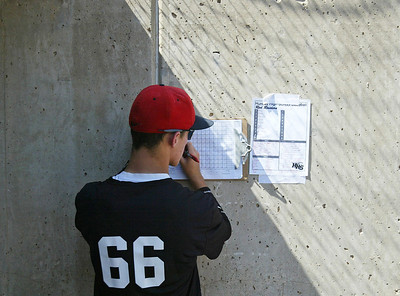 H. Rick Bamman - hbamman@shawmedia.com Huntley's Connor Reed copies the Red Raiders line up into a scoreing book in the dugout prior to the start of the Illinois High School Coaches Association's Lawler Summer Classic final 8 game at Benedictine University in Lisle Monday, July 22, 2013. Huntley ended the summer season with a 5-4, 11 inning loss to Glenbrook North.