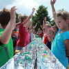 Participants raise their hands before the start of the ice cream eating contest during the Windmill City Festival Sunday in downtown Batavia. Three age groups participated in the ice cream eating contest.