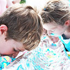 Henry White, 8, of South Elgin dives into the melting scoops of ice cream during the ice cream eating contest at the Windmill City Festival Sunday in downtown Batavia.