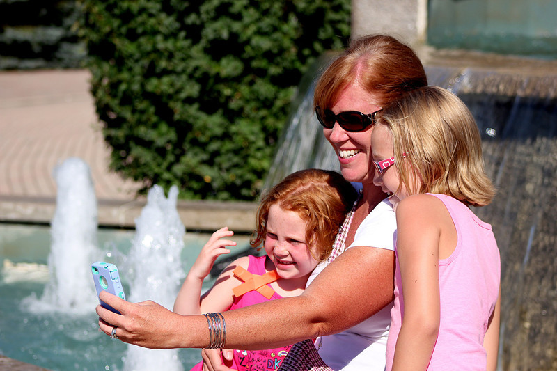Suzanne Cronley (middle), takes a picture with her daughters Kate (left), 5, and Clare (right), 7, in front of the fountain in downtown Batavia during Windmill City Festival on Friday. The festival opened on Friday and will close on Sunday.