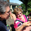 Bob Strasser of Batavia feeds his dog Wrigley, a year-old Yorkiepoo, while she is held by Sandra Butkus of Batavia before the Windmill City Festival Pet Parade in downtown Batavia on Saturday. Pet owners had the chance to enter their pet in a variety of categories, from best kisser to most unusual pet.