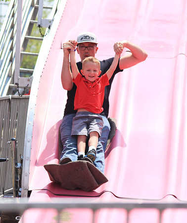 Chris Orebaugh holds his son, Reznor, 3, of Aurora, as they slip down the giant slide at the Windmill City Festival Sunday in Batavia.