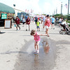 Three-year-old Sophia Reed jumps into a puddle during the second day of the Kane County Fair in St. Charles Thursday.